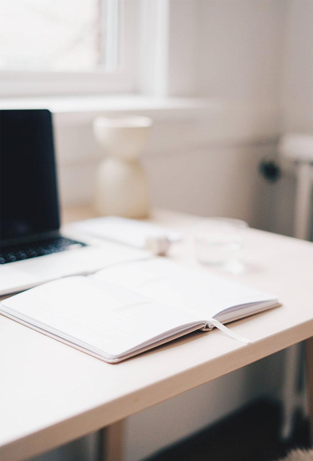 Atmos Architecture - Etude préliminaire : Photo couleur d'un carnet et d'un ordinateur sur un bureau.