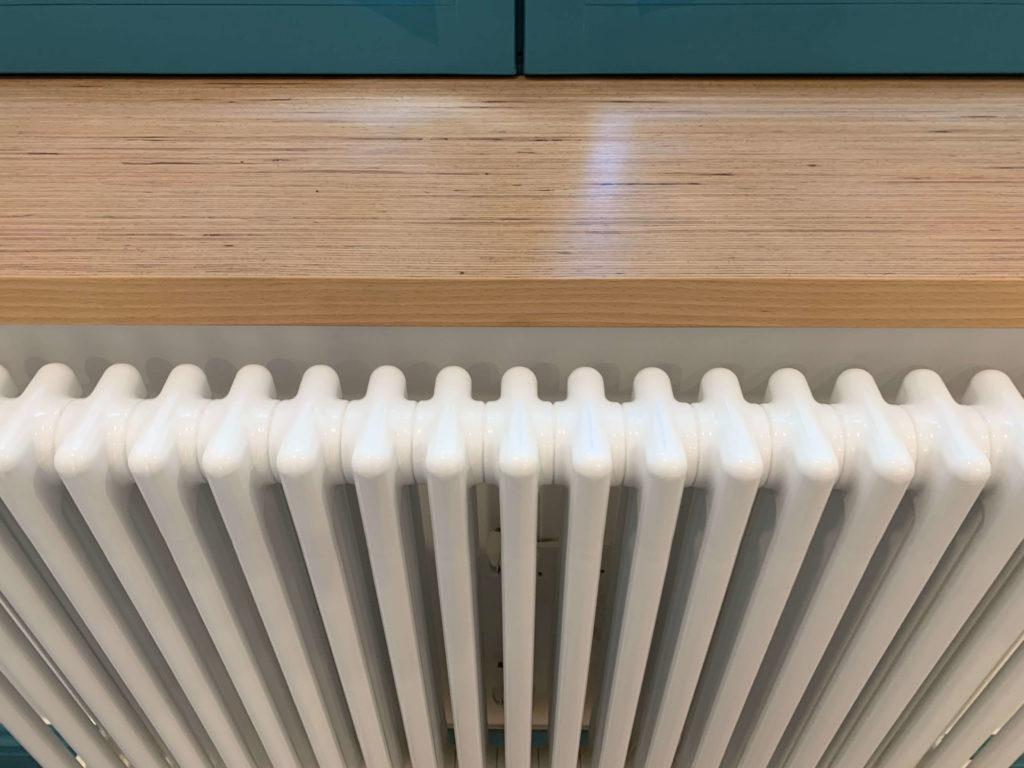 Atmos Architecture contact : photo en couleur d'un détail d'aménagement intérieur composé d'un radiateur acova, d'une allège en baubuche et d'une menuiserie bois en bleu inca.